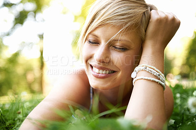 Buy stock photo Trendy and attractive young blonde woman lying on the grass outdoors with her hand in her hair