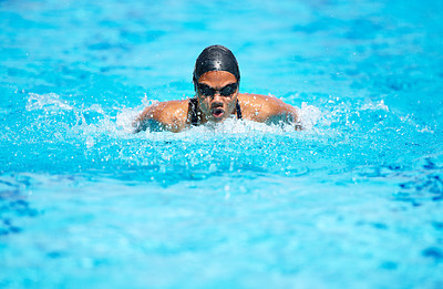 Buy stock photo Determined young female swimmer swimming within her lane in a pool