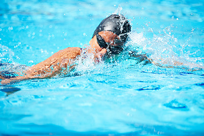 Buy stock photo Female swimmer making her way through a swimming pool stroke by stroke