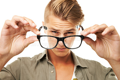 Buy stock photo Studio portrait of a young man squinting through a pair of glasses he is holding in front of him
