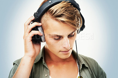 Buy stock photo Studio shot of a handsome young man listening to music on some headphones with his eyes closed