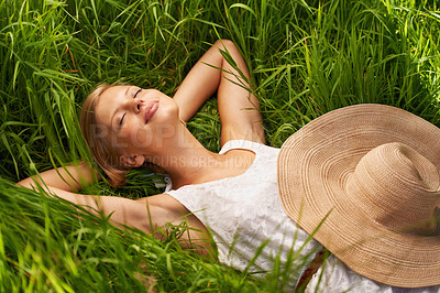 Buy stock photo An attractive young woman asleep in an open green field
