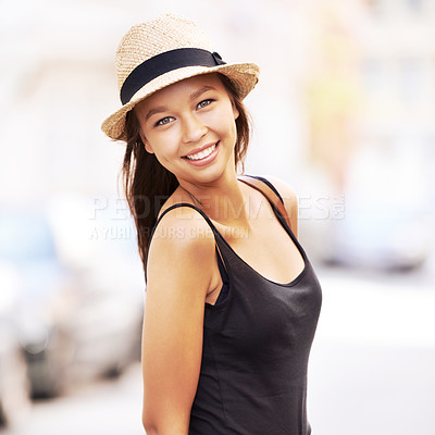 Buy stock photo A beautiful young woman with a hat standing in the street