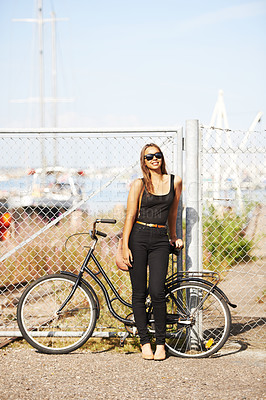 Buy stock photo A beautiful young woman standing in front of her bicycle at the harbour