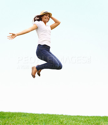 Buy stock photo Young woman leaping with joy while holding on to her hat