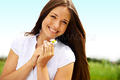 Buy stock photo Smiling young woman holding some flowers happily