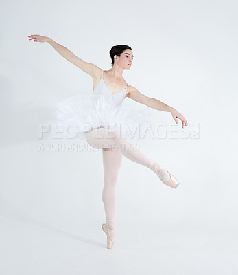 Buy stock photo Elegant young ballerina dancing en pointe against a white background