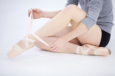 Buy stock photo Pretty young ballerina tying the ribbons on her pointe shoes while seated on white