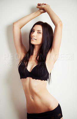 Buy stock photo Portrait of a beautiful young topless woman in a bra with her arms raised