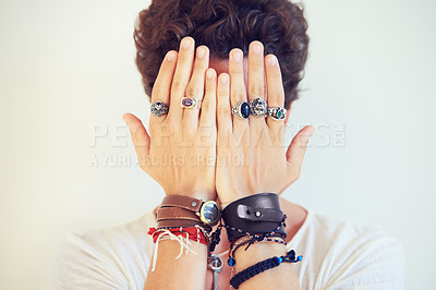 Buy stock photo Studio shot of a stylish young man wearing lots of hand accessories and holding them up in front of his face