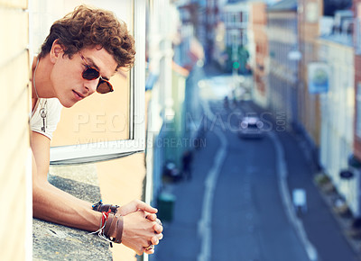 Buy stock photo A young man watching the street far below while leaning out of a window