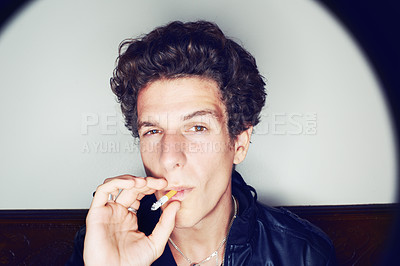 Buy stock photo Portrait of a young man inhaling deeply on a cigarette