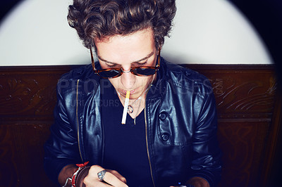 Buy stock photo Closeup shot of a young man with a cigarette hanging out of his mouth