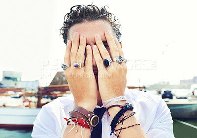Buy stock photo Close up portrait of a young man peeking through his fingers covering his face while standing on a wharf
