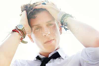 Buy stock photo Low angle portrait of a handsome and stylish young man running his hand through his wet hair