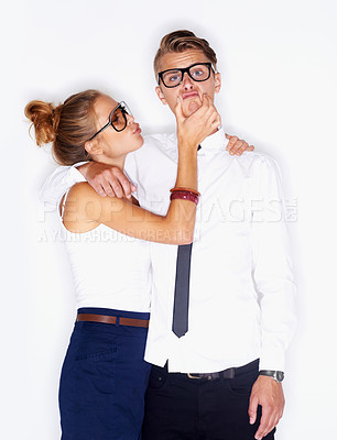 Buy stock photo Portrait of a young man wearing glasses with his face being squashed by a pretty young woman