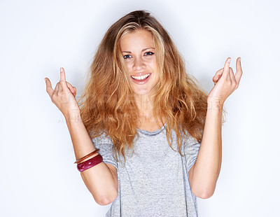 Buy stock photo Portrait of a pretty young woman making devil horns with her fingers