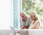 Smiling mature couple using a laptop while at home
