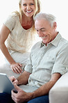 Cheerful couple using laptop computer at home