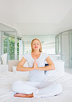 Beautiful mature woman sitting on bed meditating