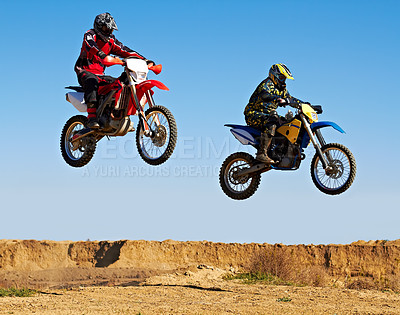 Buy stock photo Action shot of two dirt bikers mid-air