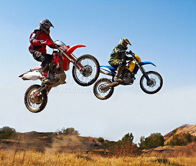 Buy stock photo Action shot of two dirt bikers jumping with their bikes over a field