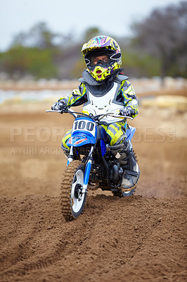 Buy stock photo A little boy riding a dirt bike on a track
