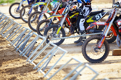 Buy stock photo A group of motocross riders waiting at the gate for the race to start