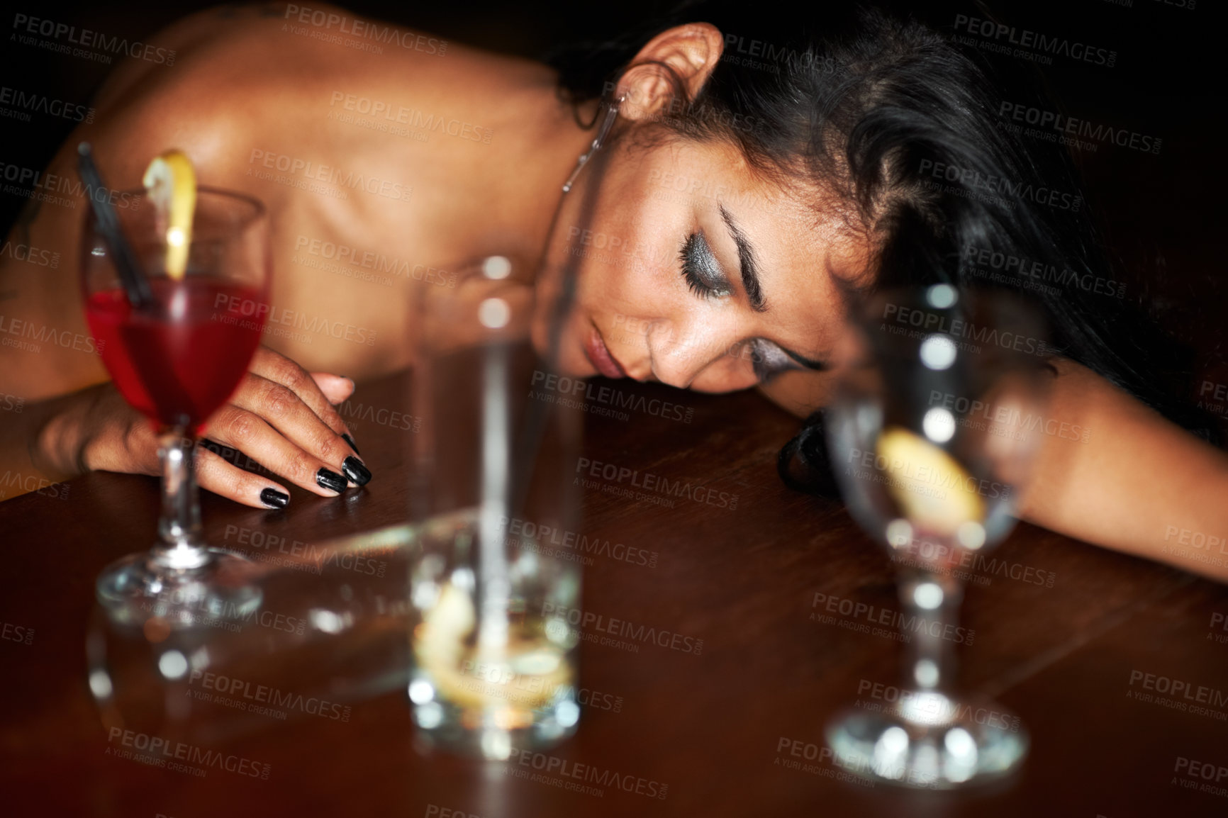 Buy stock photo A drunk young girl passed out at the bar surrounded by half-finished drinks