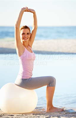 Buy stock photo Portrait of a gorgeous young woman stretching while sitting on a pilates ball