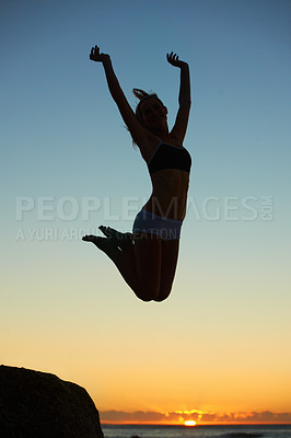 Buy stock photo Silhouette of a young woman jumping in the air at sunset