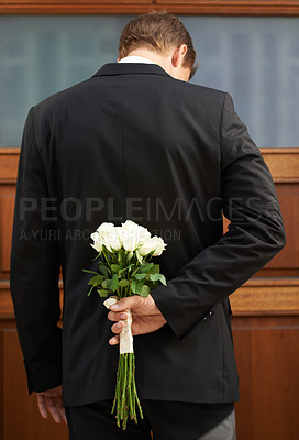 Buy stock photo A man wearing a suit holding a bunch of white roses behind his back