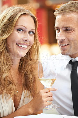 Buy stock photo A beautiful woman holds a glass of wine and enjoys her boyfriend's company