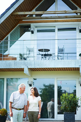 Buy stock photo Cropped shot of a mature couple standing hand-in-hand in front of their home