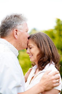 Buy stock photo Cropped shot of an affectionate senior man kissing his wife on the forehead