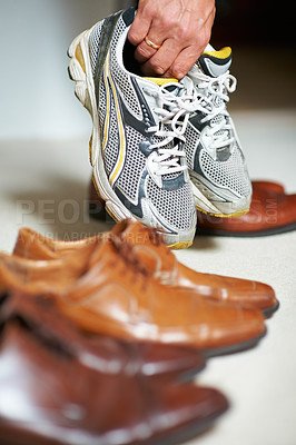 Buy stock photo Cropped shot of a man grabbing his running shoes from amongst his formal shoes