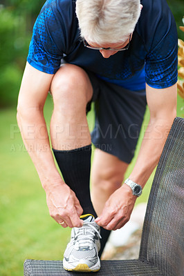 Buy stock photo Cropped shot of a jogger resting his foot on a chair while tying his shoelace