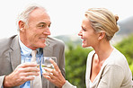 Smiling couple celebrating by toasting wine glasses