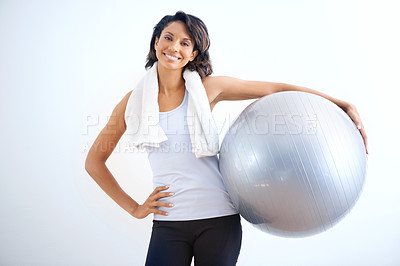 Buy stock photo A fit young beauty with a towel wrapped around her neck holding a medicine ball