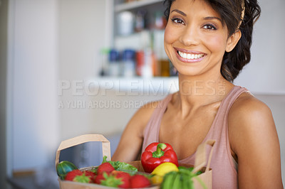 Buy stock photo Portrait of a young woman holding a paper bag of fresh produce