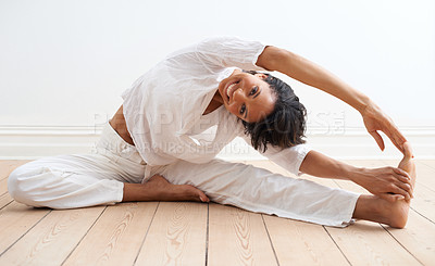 Buy stock photo A pretty young woman doing stretches before a workout