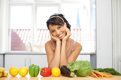 Buy stock photo Portrait of a young woman standing in a kitchen with a line of fresh produce before her
