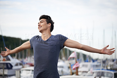 Buy stock photo A young man with arms outstretched relishing the breeze