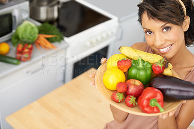 Buy stock photo Portrait of a young woman holding a bowl full of fresh produce