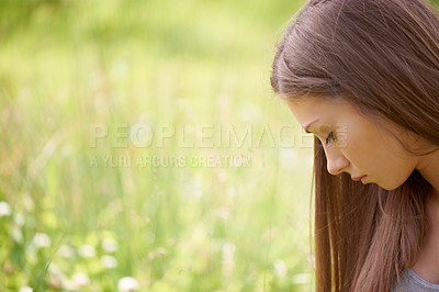 Buy stock photo A pretty young woman lost in thought while sitting in a green field