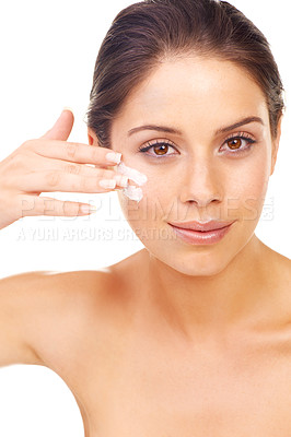 Buy stock photo Studio portrait of a beautiful young woman applying a skincare product to her face