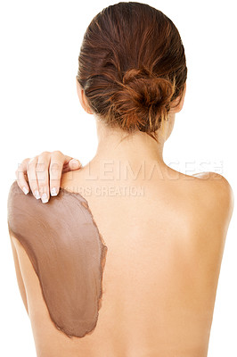 Buy stock photo Studio shot of a young woman with a mud treatment on her back