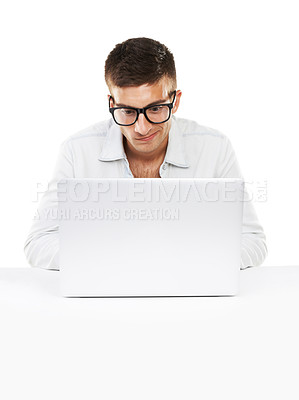 Buy stock photo A man sitting at his desk working on his laptop with hipster glasses on