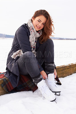 Buy stock photo Pretty teenage girl puttin on her ice skates on a natural frozen lake outdoors