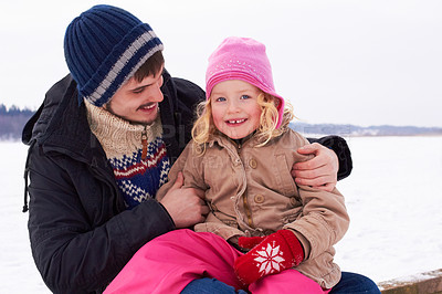 Buy stock photo Little girl sitting happily on her father's lap outside on a crisp winter's day